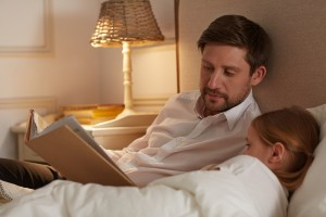Young man and his little daughter lying in bed before sleep and reading stories from book